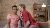 igualdade : Two young homosexual boys are sitting on the couch, american guy with short hair tells the secrete to his partner, the african boy is laughing 60 fps