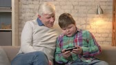 nicely : Grandfather and grandson sitting on the sofa using a smartphone, a fat child is playing on a smartphone. Young fat boy and grandfather. Home comfort, family idyll, cosiness concept. 60 fps Stock Footage