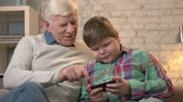nevetés : Grandfather and grandson sitting on the sofa using a smartphone, speaking, a fat child is playing on a smartphone. Young fat boy and grandfather. Home comfort, dialog, family idyll, cosiness concept. 60 fps
