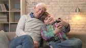 nicely : Grandfather and grandson are sitting on the sofa using a smartphone, do selfie. Young fat child and grandfather smiling, cuddling. Home comfort, family idyll, cosiness concept. 60 fps