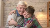 nicely : Grandfather and grandson embrace. Young fat boy and elderly grandfather. Happy family concept. 60 fps