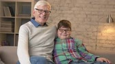 nicely : Grandfather and grandson with glasses, sitting on the couch, smiling and looking at the camera. Home comfort, family idyll, cosiness concept. 60 fps Stock Footage