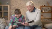 nicely : Elderly man is teaching a young fat guy. Grandfather and grandson are reading an interesting book, smiling, happy family, home cosiness concept. 60 fps