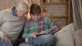 nicely : Young fat boy is sitting with his grandfather on the couch and playing on the tablet. The difference of generations. Home comfort, family idyll, cosiness concept. Clode up 60 fps Stock Footage