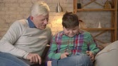 nicely : A young fat boy is sitting with his grandfather on the couch and playing on the tablet. The grandson teaches grandfather how to play on the tablet. Home comfort, family idyll, cosiness concept. 60 fps