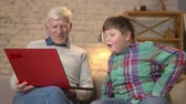 nicely : Grandfather and grandson are sitting on the couch and watching a funny, interesting movie on the laptop, laughing. Home comfort, family idyll, cosiness concept, difference of generations 60 fps