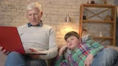 nicely : Grandfather and grandson are sitting on the couch and watching an interesting video on the laptop. The young fat boy is bored. Difference of generations. Home comfort, family idyll, cosiness concept. 60 fps