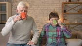 nicely : Grandfather and grandson are sitting on the couch and drinking tea, coffee, looking at the camera. An old man and a young fat boy are sitting on the couch. Home comfort, family idyll, cosiness concept, difference of generations. 60 fps