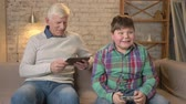 cosiness : Grandfather and grandson are sitting on the couch. An old man uses a tablet, a young fat guy plays on the console game, passionate. Video games. Home comfort, family idyll, cosiness concept, difference of generations 60 fps