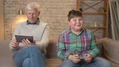 nicely : Grandfather and grandson are sitting on the couch. An old man uses a tablet, a young fat guy plays on the console game, happy, smiling. Video games. Home comfort, family idyll, cosiness concept, difference of generations 60 fps Stock Footage