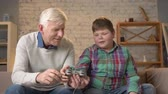 nicely : The grandson teaches grandfather to play the console game. An elderly man is learning how to play a fighting video game. Home comfort, family idyll, cosiness concept, difference of generations 60 fps