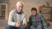 nicely : Grandpa plays in the console video game sitting on the couch with his grandson. An elderly man sits on the couch and holds game controller playing video games. Home comfort, family idyll, cosiness concept, difference of generations. 60 fps