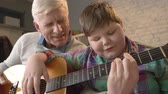 nicely : Grandfather is teaching his grandson how to play the guitar. An elderly man is teaching a young fat child to play guitar. Home comfort, family idyll, cosiness concept, difference of generations, close up 60 fps