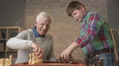 kavga : Grandfather and grandson are preparing to play chess. An elderly man teaches a fat child how to play chess. Expose the pieces on the chessboard. Home comfort, family idyll, cosiness concept, difference of generations, close up. 60 fps Stok Video