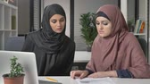 keypad : Two beautiful young girls in hijabs sit in the office and discuss schedules, business, dialogue, conversation. 60 fps