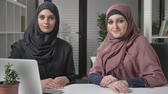 islam : Two young girls in hijab sit in the office with a look at the camera. Smiling. 60 fps Stok Video