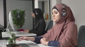 arabesco : A young beautiful girl in a pink hijab is talking on the headset, answering calls in call center. Arab women in the office. 60 fps