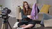poznámky : Young red-haired girl blogger, smiling, talking at the camera, showing a new purchase, clothes, jacket, dress, top, home comfort in the background. 60 fps.