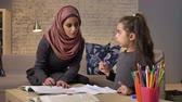 cosiness : Young beautiful mother in hijab doing homework with her little daughter, training, homework, learns to read, home comfort in the background, colored pencils 50 fps Stock Footage