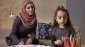 младенчество : Young beautiful mother in hijab makes lessons, little daughter chooses color pencils, draws, childrens coloring, home comfort in the background, colored pencils 50 fps Стоковые видеозаписи