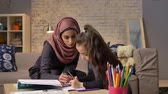 младенчество : Young beautiful mother in hijab doing homework lessons, little daughter chooses color pencils, draws, childrens coloring, home comfort in the background, colored pencils 50 fps