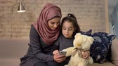 младенчество : Young beautiful mother in hijab with little girl on couch, smiling, uses smartphone, makes selfie, cuddling, little girl with teddy bear, home comfort in the background 50 fps