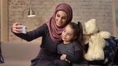 относительный : Young beautiful mother in hijab with little girl on couch, smiling, uses smartphone, makes selfie, cuddling, little girl with teddy bear, home comfort in the background 50 fps