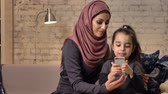 младенчество : Young beautiful mother in hijab with little girl on couch, smiling, little girl uses a smartphone, makes selfie, little girl with teddy bear, happy family, concept home comfort in the background 50 fps