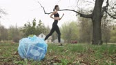 dürtmek : Close-up of garbage in the park, jogging girl in black suit in the background blurred, plogging concept, 50 fps Stok Video