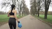 zametání : Young athletic girl in a black sport suit runs through green summer park with a trash bag in her hand, plogging concept, back side view 50 fps