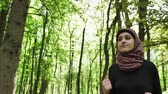 марафон : Young athletic girl in hijab running, jogging in green park, forest, front side view 50 fps