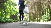 dürtmek : Plogging concept, young girl in hijab runs through park and cleans up garbage. 50 fps