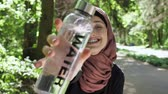 serious : Portrait of a cute young girl in a hijab with a bottle of water in her hands, smiling, looking at the camera, park in the background, focus pull 50 fps