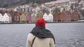 solitário : Silhouette of a man in a red hat standing by the water, colorful houses in the background 50 fps