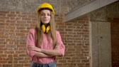 нахальный : Young confident girl builder is crossing arms, raising eyebrow, nodding her head, watching at camera, brick background