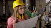 zaměstnavatel : Young serious girl builder is watching plan of building, thinking