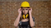 headpiece : Young beautiful attractive women in helmet looking straight into camera and putting on glasses, female builder, brick background Stock Footage