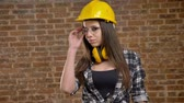 lovable : Young pretty attractive women in helmet looking straight into camera and taking off glasses, female builder, brick background Stock Footage