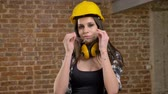 headpiece : Beautiful cute young women in helmet and headphones looking straight into camera and putting on glasses, female builder, brick background