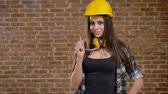 headpiece : Beautiful attractive young women in helmet and headphones looking straight into camera and holding her glasses, smiling, female builder, brick background
