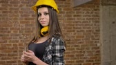 bricklayer : Beautiful attractive young women in helmet and headphones looking straight into camera and holding wrench, smiling, female builder, brick background