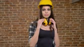 headpiece : Beautiful attractive young women in helmet and headphones walking towards camera and giving air-kiss, female builder, brick background Stock Footage