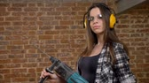 perforator : Beautiful attractive young women in glasses and headphones holding drill and looking into camera, female builder, brick background