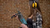 headpiece : Beautiful attractive young women in glasses and headphones holding drill and looking into camera, posing with perforator, female builder, brick background Stock Footage