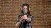 perforator : Beautiful attractive young women in glasses and headphones pointing drill into camera and blowing on perforator, female builder, brick background