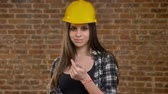 tentador : Young pretty attractive women in helmet looking into camera and inviting somebody with her fingers, confident, smiling, female builder, brick background