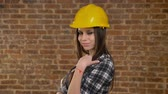 ocupação profissional : Young pretty attractive women in helmet looking into camera and inviting somebody with her finger, confident, smiling, female builder, brick background Stock Footage