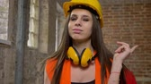 headpiece : Young charming attractive women in helmet and earphones looking and pointing in camera, twisting her long hair, female builder, brick building background