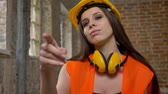 headpiece : Young beautiful attractive women in helmet and earphones pointing in camera and inviting somebody, female builder, brick building background Stock Footage