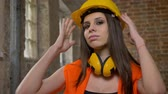 headpiece : Young pretty attractive women in helmet and earphones looking in camera, touching and adjusting casque, crossing hands, female builder, brick building background Stock Footage